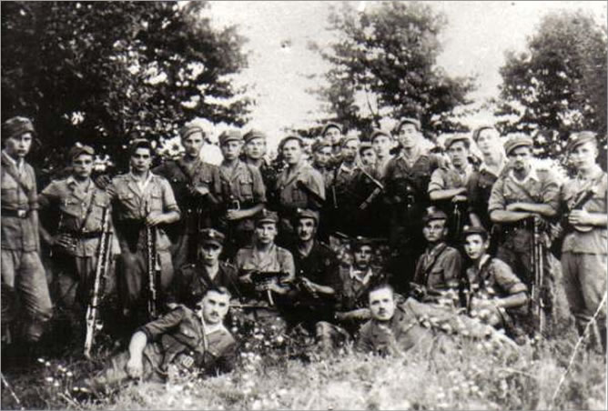 "Władzin Village (in Uchanie Municipality, Hrubieszów County); beginning of August 1946, few moments before the partisans met with British journalist, W.D. Selby. Standing from left are: Lucjan Kisiel, nom de guerre ""Lutek"", Roman Kaszewski, ""Zdybek"", Roman Koccęmirowski, ""Jar"", Mieczysław Hawryluk, ""Syrena"", Czesław Skiba, ""Granit"", NN (pol. abr. Unknown and Unidentified – Nieznany i Niezidentifikowany) soldier, nom de guerre ""Błysk"", Ryszard Gałecki, ""Grom"", Eugeniusz Kulik, ""Wicher"", Bogdan Sołdun, ""Majtek"", NN soldier, nom de guerre ""Poruta"", Czesław Jarosz, ""Hiena"", Leon Piekut, """"Orzeł"", Lieuenant Mieczyslaw Niedzielski, ""Grot"" (Lewczuk's deputy officer), Piotr Lichaczewski, ""Piter"", Janusz Flach, ""Pazur"", Roman Matejski, """"Skała"", Jan Fic, ""Ryś"". Kneeling from left are: NN, """"Słodki"", NN, ""Zdziebko"", NN soldier, ""Miś"", Jerzy Śliwiński, ""Śliwa"", Jan Madejski, ""Szabla"", Jerzy Baran, ""Poreba"". At the bottom, from left are: Lieutenant Henryk Lewczuk, nom de guerre ""Młot"" (the unit's commander), and Mieczyslaw Patkowski, nom de guerre ""Gruby""."