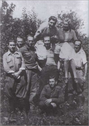 "This picture was taken probably in 1945. The 3rd from left is Czesław Hajduk, nom de guerre ""Ślepy"", who will later command the WiN's tactical unit subordinated to the III WiN Hrubieszów District; 4th from the left is Stanisław Sekuła, nom de guerre ""Sokół"" who commanded an assault team of the Home Army (AK). His post is later assumed by Henryk Lewczuk ""Młot""; 1st from right is Stefan Bakuniak, nom de guerre ""Watażka"" (a close aide of the ""Ślepy""); the girl in the photo is Halama from the forester's station in the nearby Wojsławice. Her brothers were collaborating with ""Sokół""."