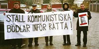 "Demonstrators in Storvreta, Sweden - ""We demand that the Communist tormentors be brought to justic""."